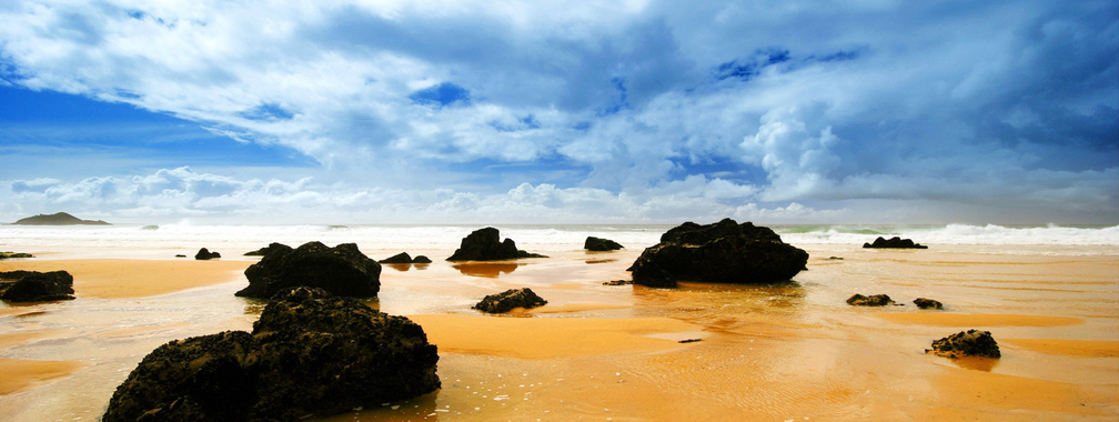 Orange ocean and black rocks beach wallpaper