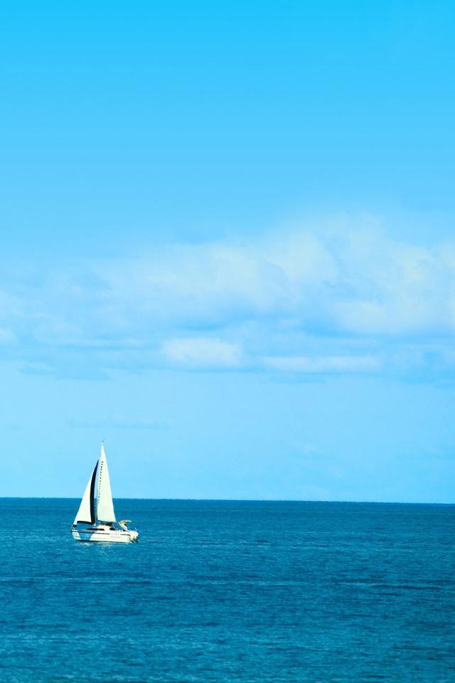 White Sailboat On Blue Ocean Beach Background