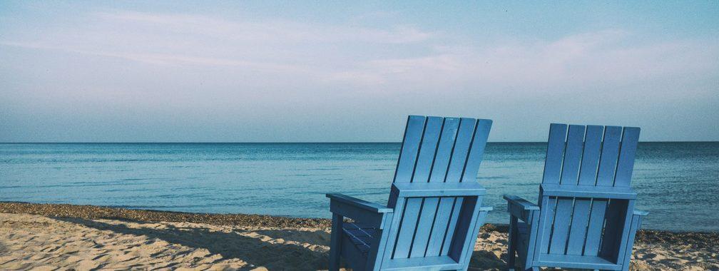 Adirondack chairs on the sandy beach