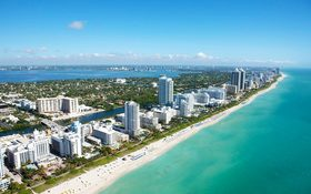 Aerial view of stunning buildings next to a white beach at Miami Beach, FL, USA