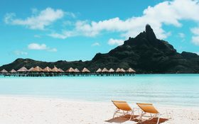 Charming tropical island with cottages and beach chairs in French Polynesia