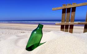 Green bottle on sandy beach wallpaper
