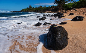 Ocean waves crashing on lava rocks on Ho'okipa Beach in Maui, Hawaii