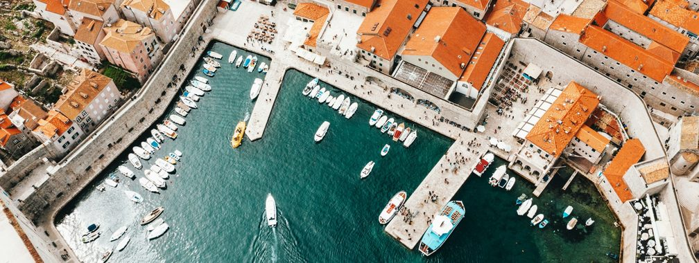 Old city port with moored ships and historical houses in Dubrovnik, Croatia
