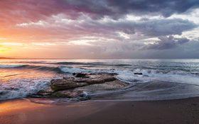 Stormy orange beach sunrise at Playa de la Misericordia, Spain