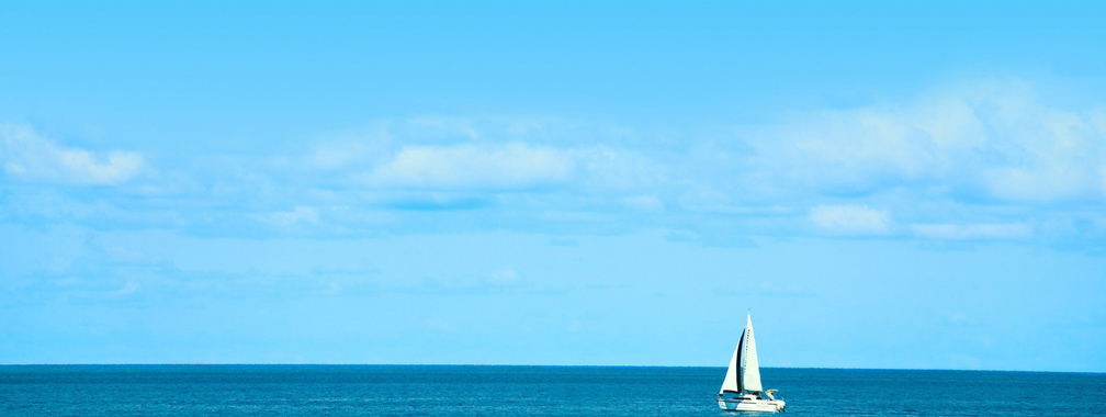 White Sailboat on Blue Ocean Beach Background